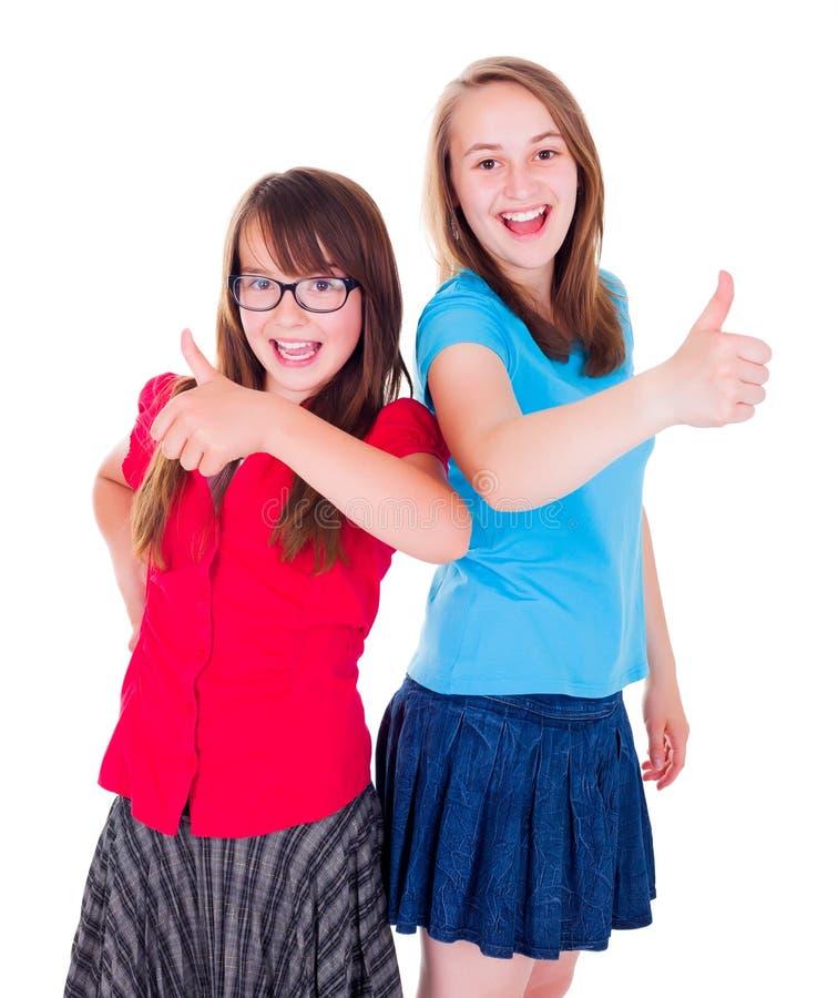 Meninas adolescentes que levantam-se e que mostram os polegares fotografia de stock