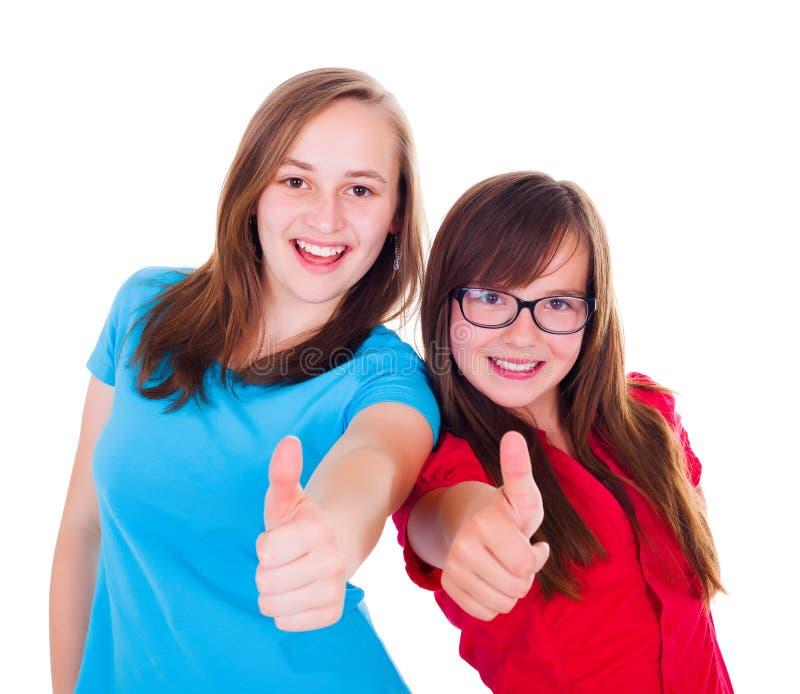 Meninas adolescentes que mostram os polegares acima fotografia de stock
