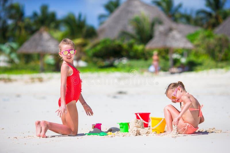 Meninas adoráveis durante férias de verão As crianças que jogam com praia brincam na praia branca imagem de stock royalty free