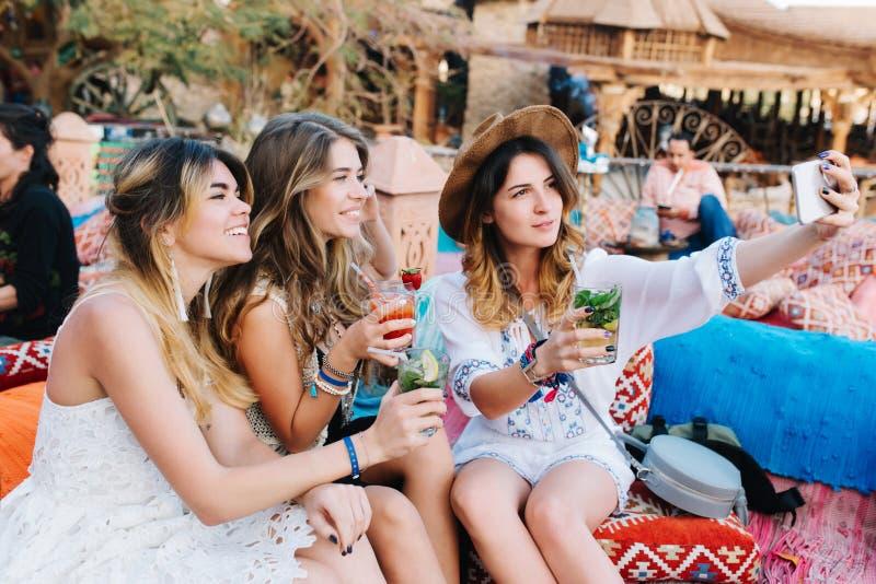 Meninas adoráveis na roupa à moda que descansa após a compra e a fatura do selfie, ao beber cocktail mulher nova curly imagem de stock