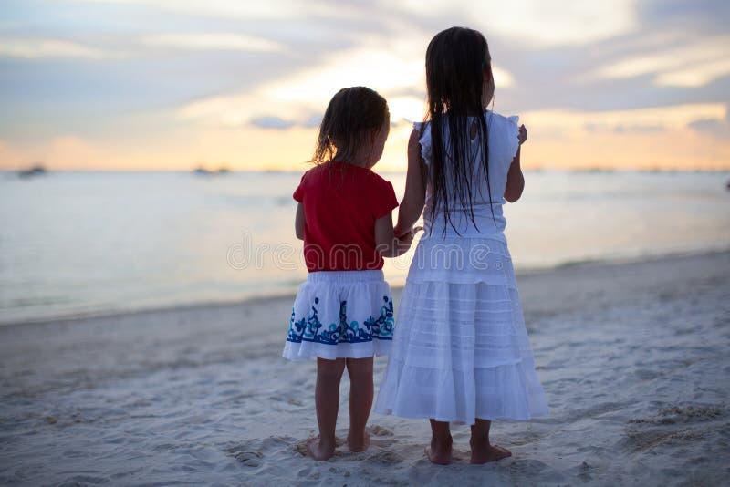 Meninas adoráveis pequenas no vestido agradável na praia fotos de stock royalty free