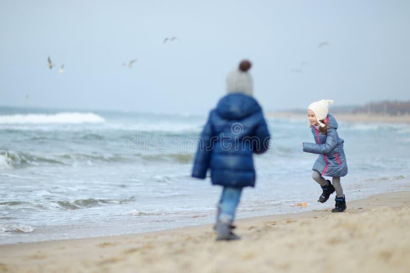 Meninas adoráveis que jogam pelo oceano fotografia de stock