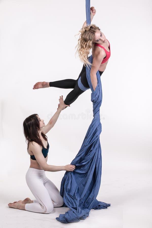 Meninas agradáveis e ajuda em exercícios dos esportes foto de stock