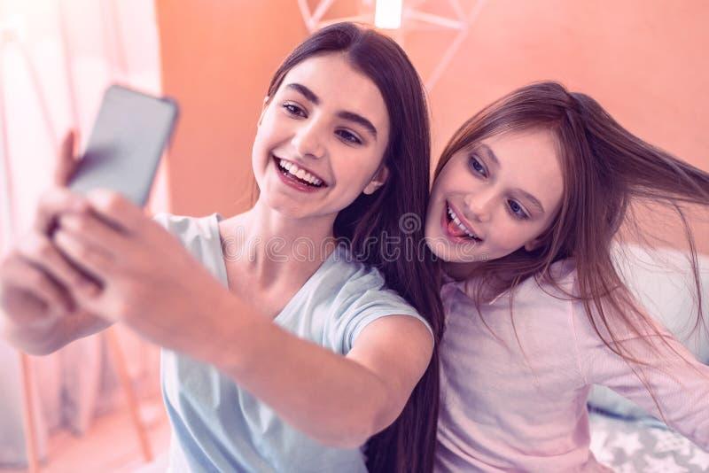 Meninas agradáveis que tentam fazer o selfie para redes sociais imagens de stock