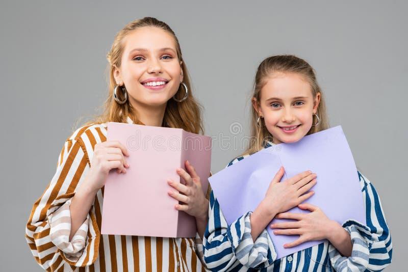 Meninas alegres de sorriso que levam firmemente papéis coloridos foto de stock