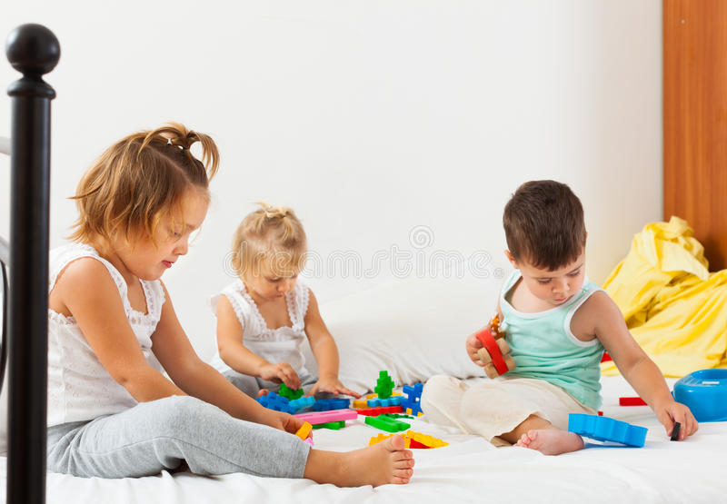 Meninas alegres e um menino que joga na cama grande fotografia de stock