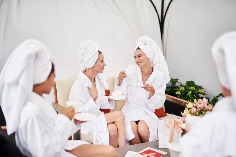 Meninas alegres que apreciam bebidas quentes e que conversam na sala de estar dos termas imagem de stock royalty free