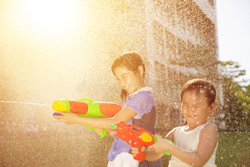 Meninas alegres que jogam armas de água no parque fotos de stock