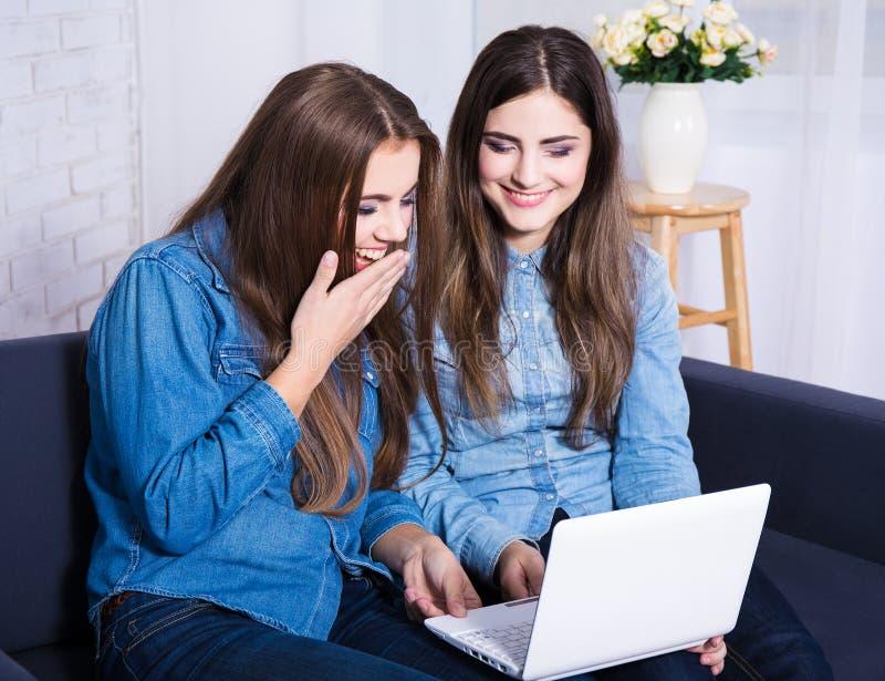 Meninas alegres que procuram algo no portátil em casa fotografia de stock