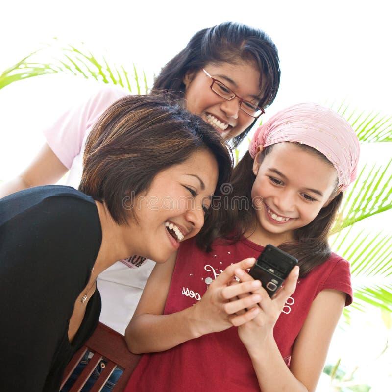 Meninas asiáticas da família que compartilham de um riso imagens de stock royalty free