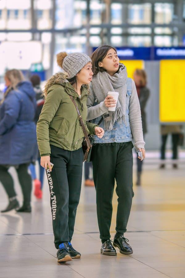 Meninas asiáticas que olham a tela da informação na estação de trem central de Utrecht, Países Baixos imagem de stock royalty free