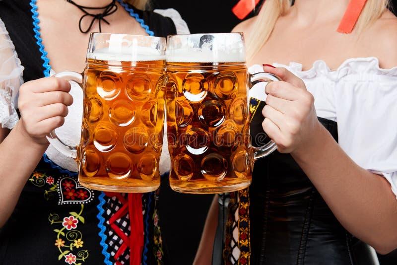 Meninas bávaras novas e bonitas com as duas canecas de cerveja no fundo preto imagem de stock