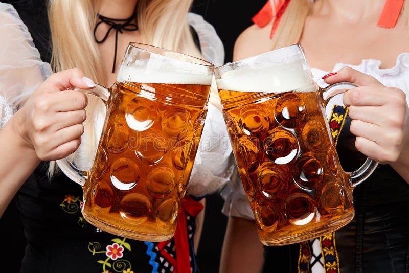 Meninas bávaras novas e bonitas com as duas canecas de cerveja no fundo preto fotos de stock
