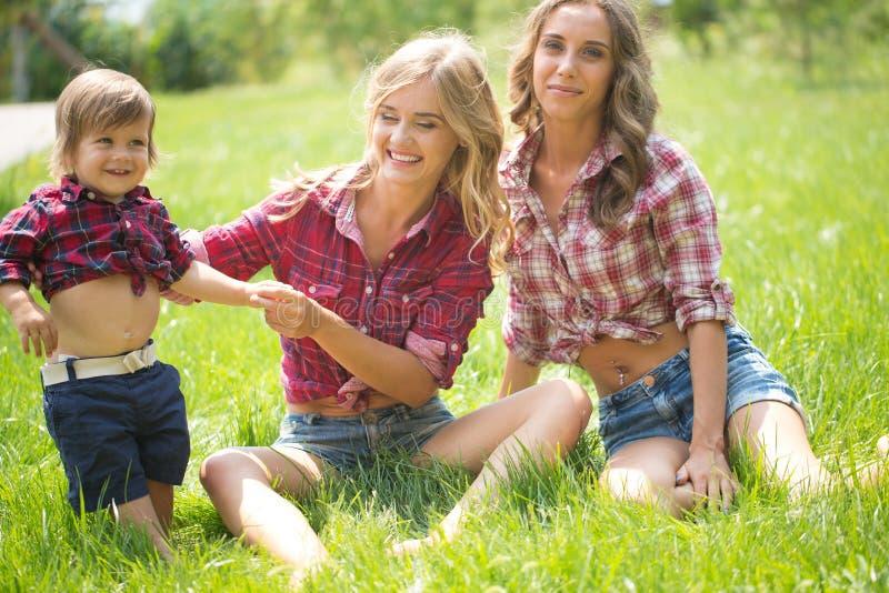 Meninas bonitas com o rapaz pequeno na grama imagens de stock royalty free