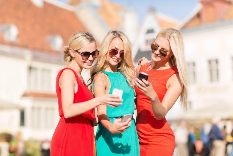 Meninas bonitas com os smartphones na cidade foto de stock