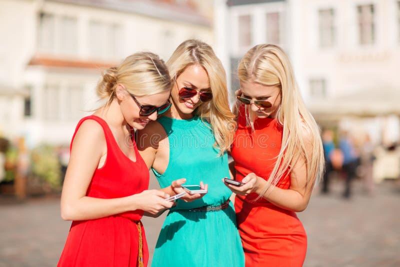 Meninas bonitas com os smartphones na cidade imagem de stock royalty free