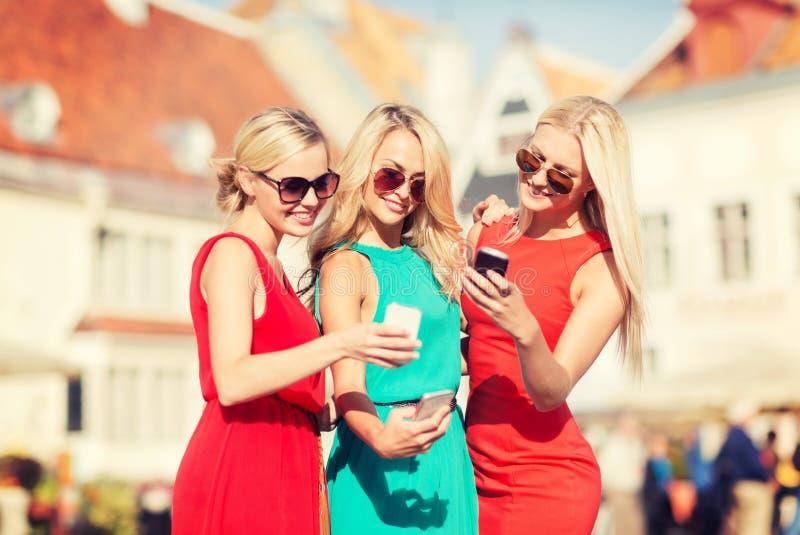 Meninas bonitas com os smartphones na cidade fotos de stock