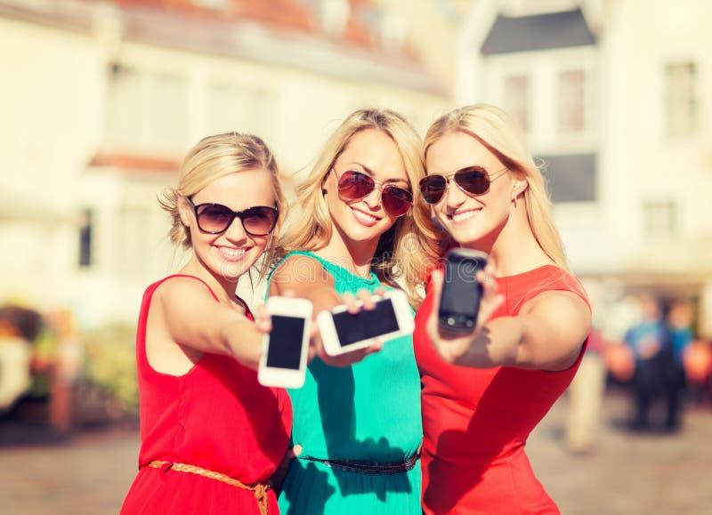 Meninas bonitas com os smartphones na cidade imagem de stock