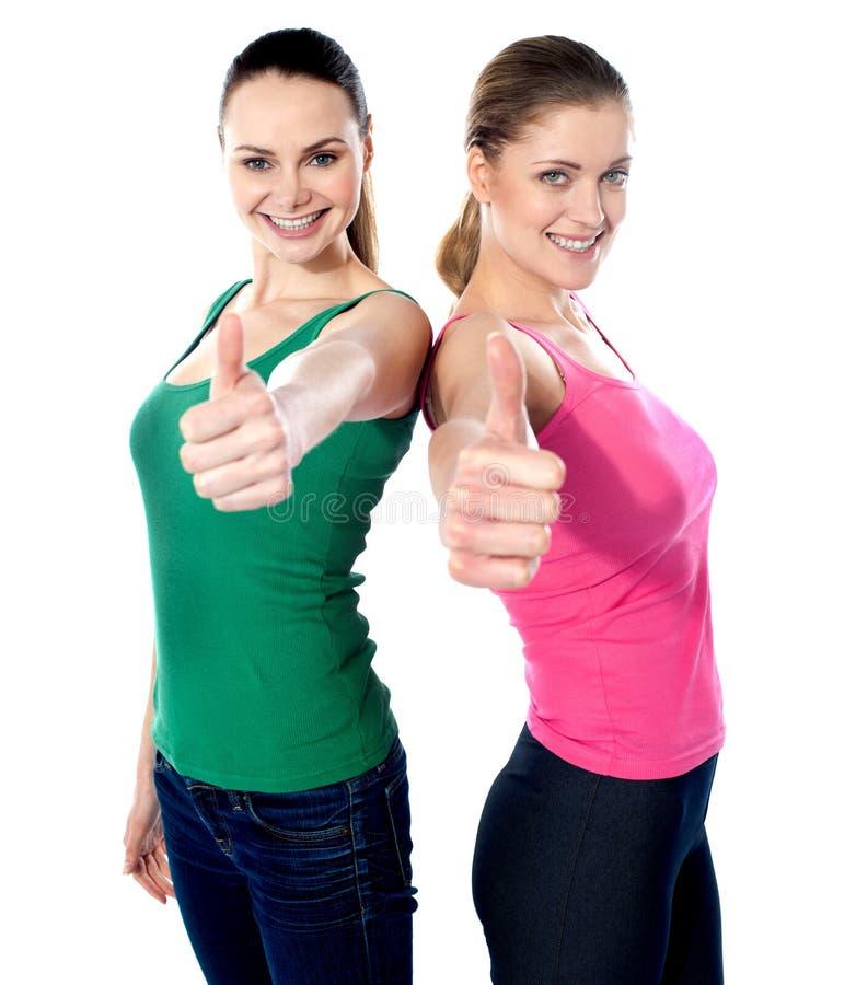 Meninas bonitas de sorriso que gesticulam o thumbs-up fotografia de stock