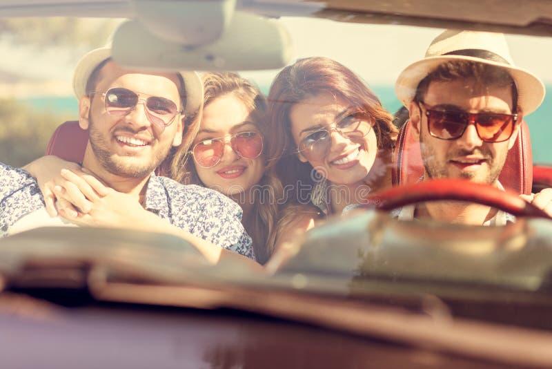 Meninas bonitas do amigo do partido que dançam em um carro na praia feliz imagem de stock royalty free