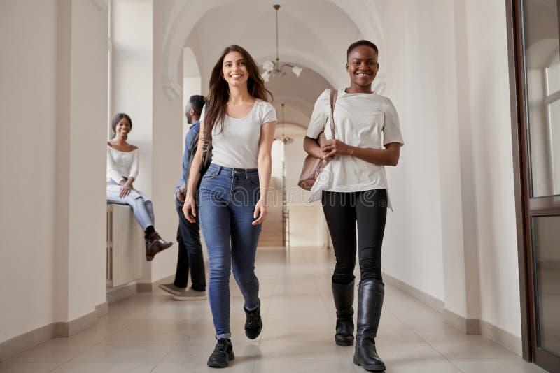 Meninas bonitas dos estudantes caucasianos e africanas fotografia de stock
