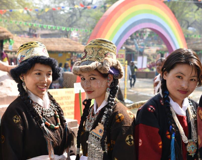 Meninas bonitas em vestidos tribais indianos tradicionais e em apreciar a feira