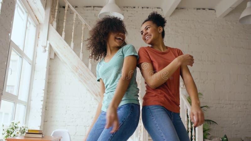 Meninas bonitas novas da raça misturada que dançam em uma cama junto que tem o lazer do divertimento no quarto em casa fotografia de stock