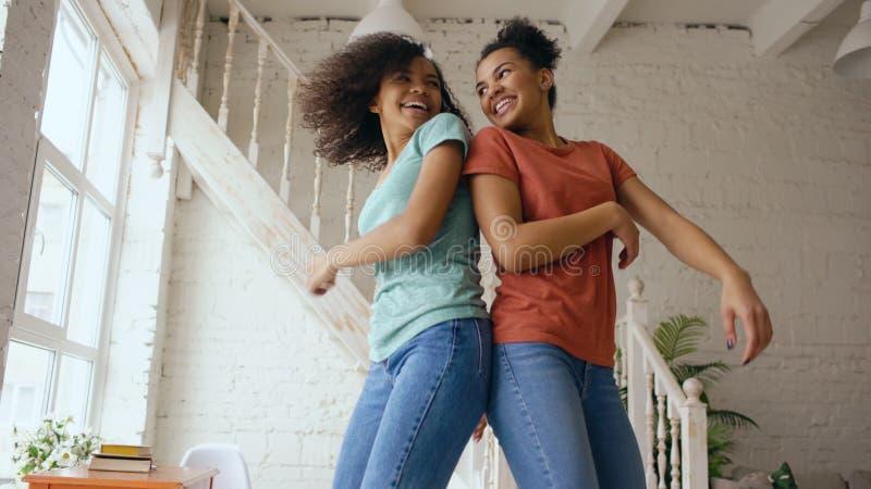 Meninas bonitas novas da raça misturada que dançam em uma cama junto que tem o lazer do divertimento no quarto em casa imagens de stock royalty free