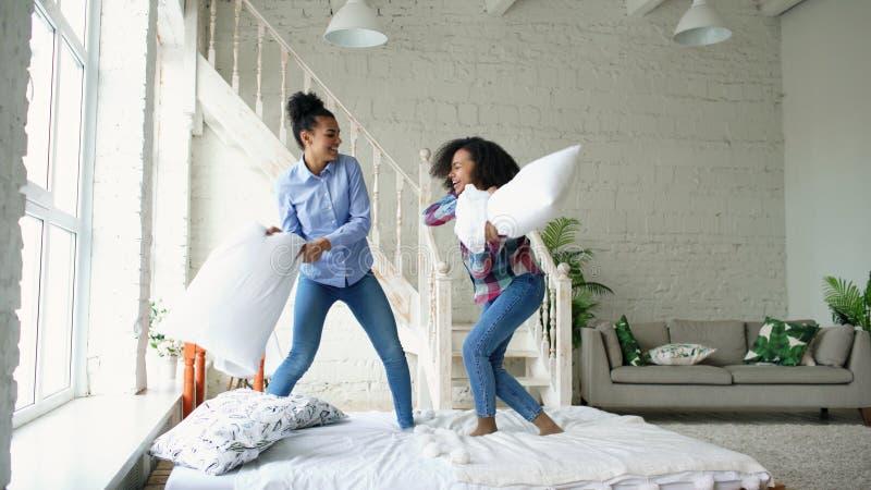 Meninas bonitas novas da raça misturada que saltam nos descansos da cama e da luta que têm o divertimento em casa imagens de stock royalty free