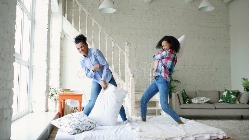 Meninas bonitas novas da raça misturada que saltam nos descansos da cama e da luta que têm o divertimento em casa fotografia de stock