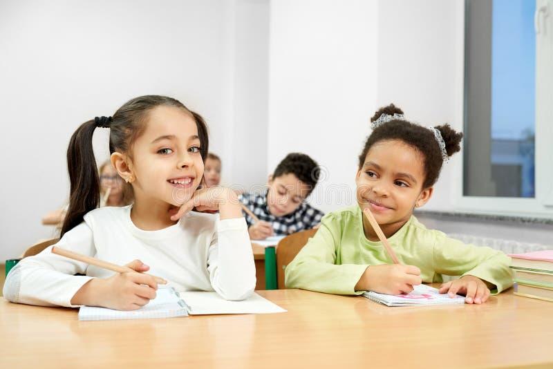 Meninas bonitas que levantam na sala de aula ao estudar na escola imagem de stock royalty free