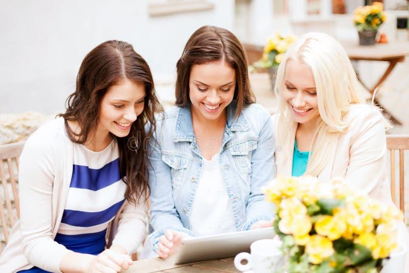 Meninas bonitas que olham o PC da tabuleta no café imagem de stock