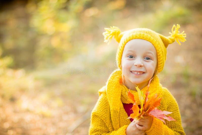 Meninas bonitos com os olhos grandes do bue que jogam no dia bonito do outono Crianças felizes que têm o divertimento no parque d fotos de stock