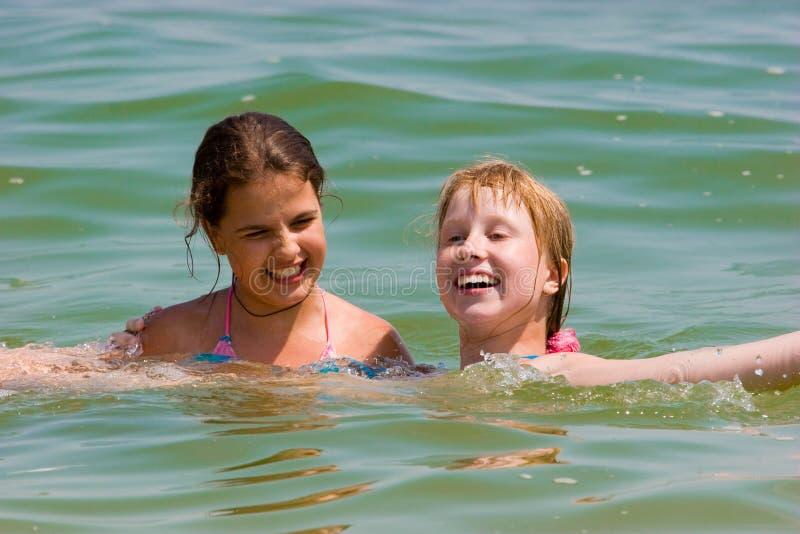 Meninas bonitos do adolescente que jogam na água de mar imagens de stock