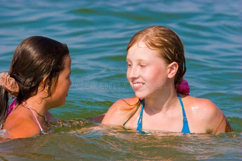 Meninas bonitos do adolescente que jogam na água de mar imagens de stock royalty free