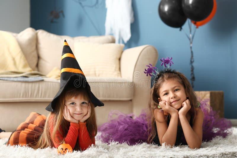 Meninas bonitos em trajes de Dia das Bruxas em casa foto de stock royalty free
