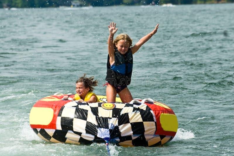 Meninas bonitos na câmara de ar atrás do barco imagem de stock royalty free