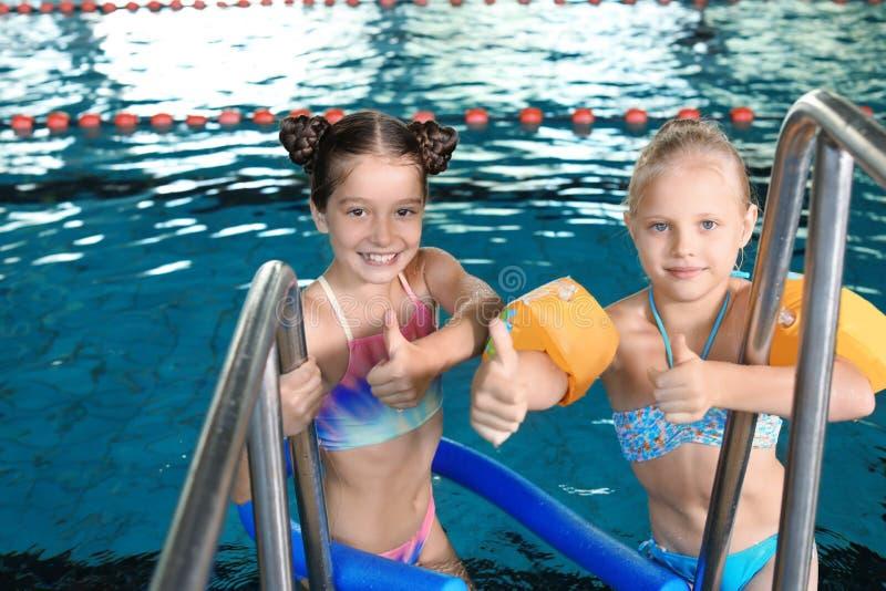 Meninas bonitos na piscina interior imagem de stock