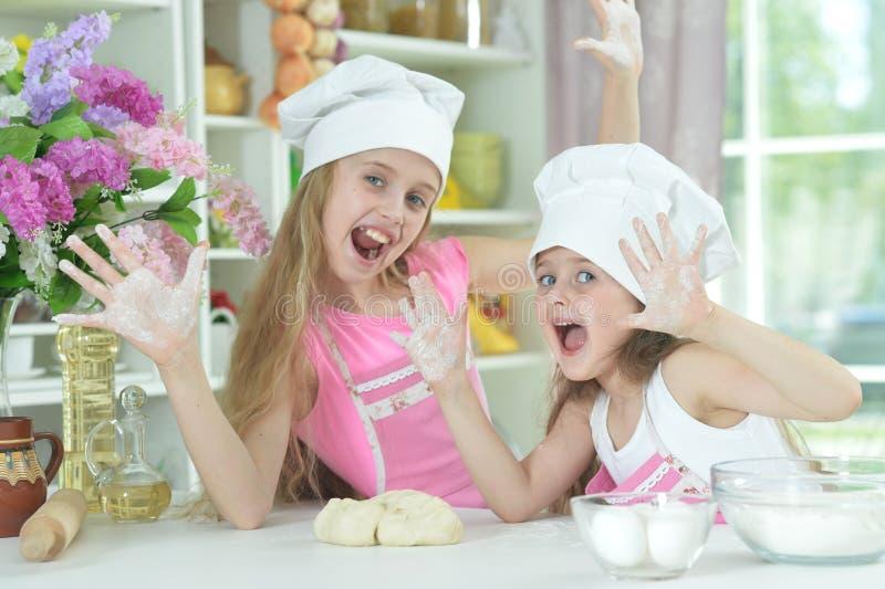 Meninas bonitos nos chapéus dos cozinheiros chefe que fazem a massa fotos de stock
