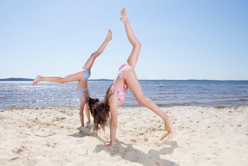 Meninas bonitos que fazem a aptidão em uma praia fotos de stock royalty free