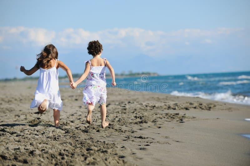 Meninas bonitos que funcionam na praia fotos de stock