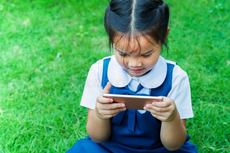 Meninas bonitos que jogam o Internet com o smartphone móvel na grama fotografia de stock
