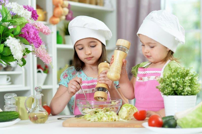 Meninas bonitos que preparam a salada fresca deliciosa na cozinha fotografia de stock royalty free