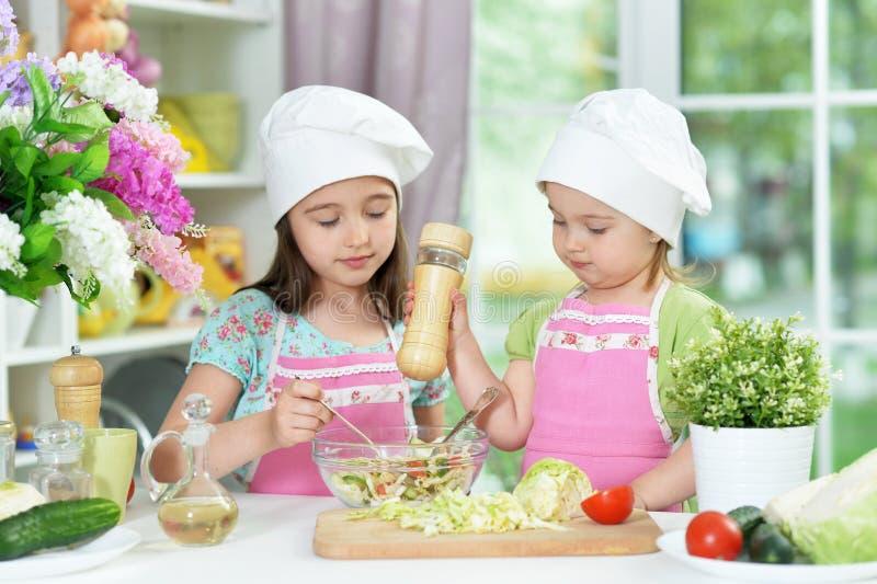 Meninas bonitos que preparam a salada fresca deliciosa na cozinha fotografia de stock