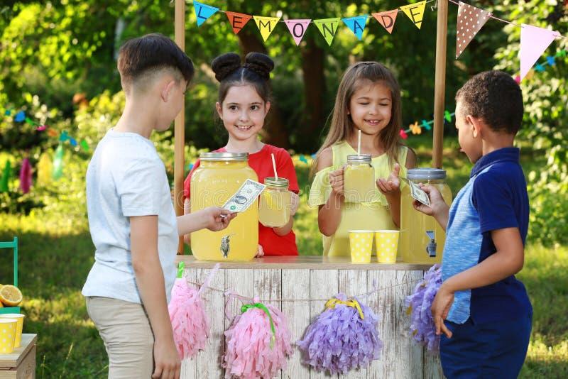 Meninas bonitos que vendem a limonada natural aos meninos Bebida de refrescamento do ver?o imagem de stock