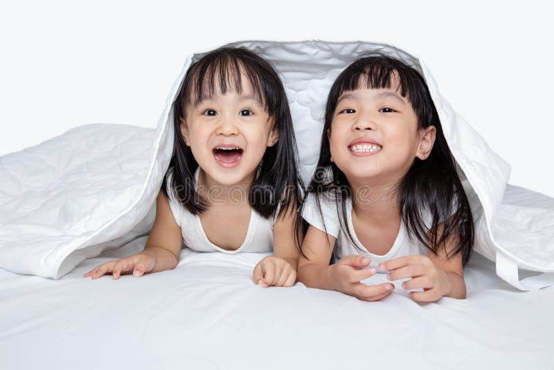 Meninas chinesas pequenas asiáticas que jogam na cama foto de stock royalty free
