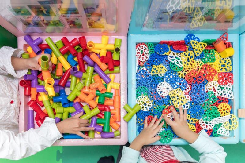 Meninas chinesas pequenas asiáticas que jogam o enigma fotos de stock