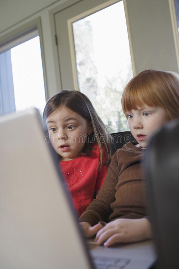 Meninas chocadas que usam o portátil em casa imagem de stock