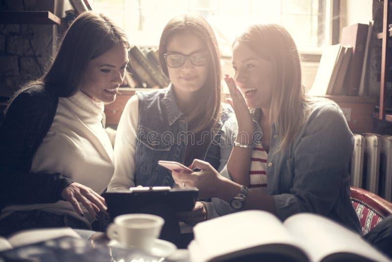 Meninas chocadas smiley que usam o móbil no café imagem de stock