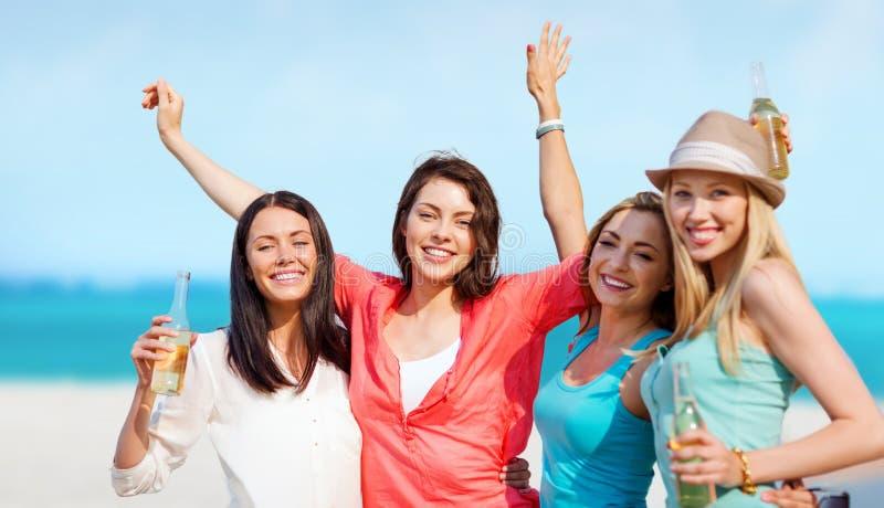 Meninas com bebidas na praia imagens de stock royalty free